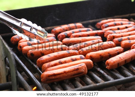 Rows of hot dogs on barbeque grill at park - stock photo