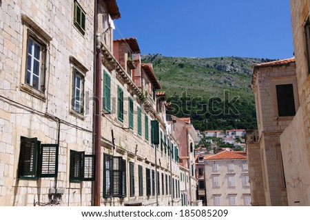 Rows of houses with several windows close to an area with hills. - stock photo