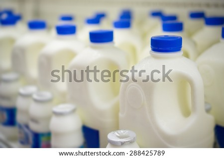 Rows of large milk bottles in fridge in supermarket - stock photo