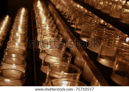 Rows of lit candles in a catholic church