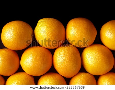 Rows of many ripe fresh oranges isolated on black background. Front view closeup - stock photo