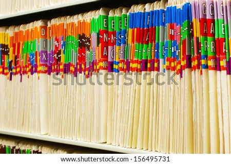 Rows of medical files with colorful tabs - stock photo