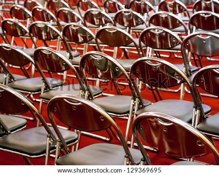 Rows of metal chairs at the conference in an empty room. Back view - stock photo