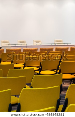 Rows of new yellow chairs in the conference hall