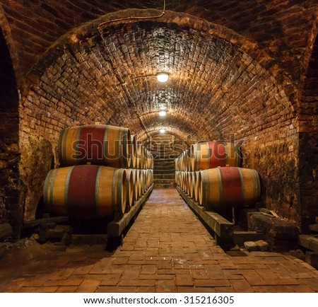 Rows of oak barrels in underground wine cellar
