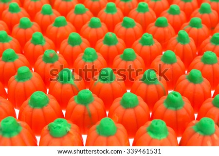 Rows of orange and green Halloween pumpkin candy on a white table top. - stock photo