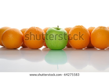 rows of oranges and a green apple in the middle - stock photo