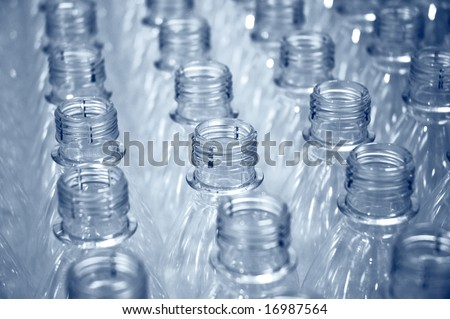 rows of plastic bottles on a factory production line - stock photo