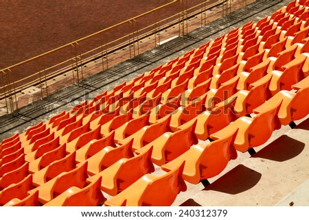 Rows of plastic chairs in a football stadium. - stock photo