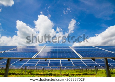 Rows of polycrystalline photovoltaic modules on the background of the cloudy sky - stock photo