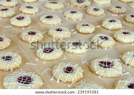 Rows of raspberry thumbprint cookies with powdered sugar frosting drizzle sitting on wax paper - stock photo
