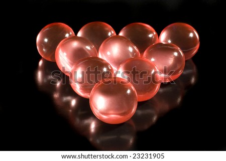 Rows of red aromatic bath balls (on a black background, with beautiful reflections) - stock photo