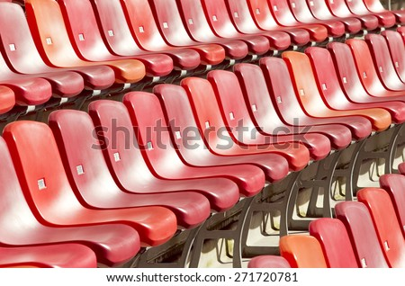 rows of red chairs in a sports stadium on a hot summers day - stock photo