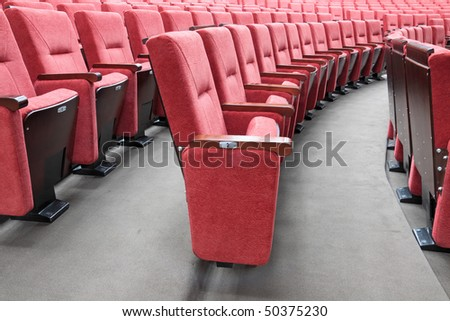 Rows of red folding chairs in conference room - stock photo