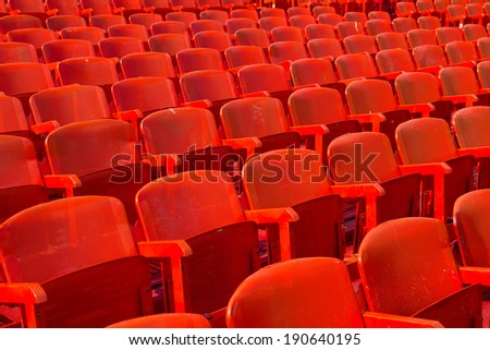 Rows of red metal chairs in arena