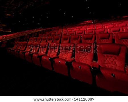 Rows of red movie theater seats in dark surrounding - stock photo