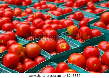 Rows of red ripe tomatoes in blue boxes at the farmers market - stock photo