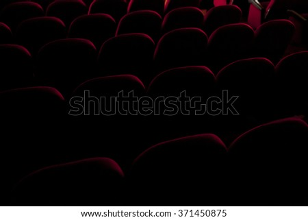 Rows of red velvet seats in a cinema or theater / theatre stage, seen from behind in semi-darkness. Close-up angled shot.  - stock photo