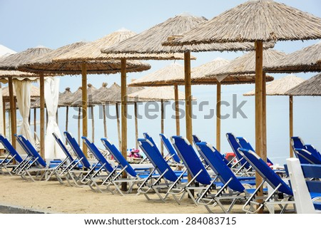 Rows of reed umbrellas and blue deck chair on the sea beach  - stock photo