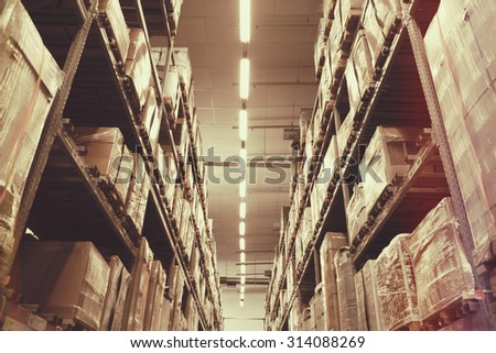 Rows of shelves with boxes in factory warehouse, light leak filter. - stock photo