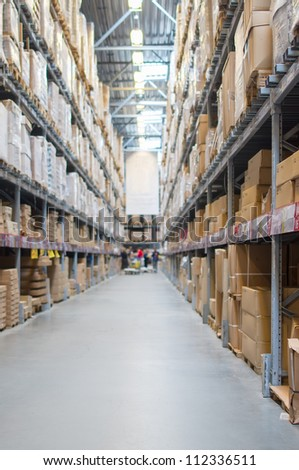 Rows of shelves with boxes in modern warehouse - stock photo