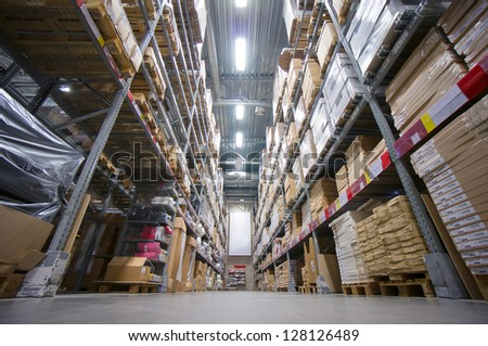 Rows of shelves with cardboard boxes on modern warehouse in store - stock photo
