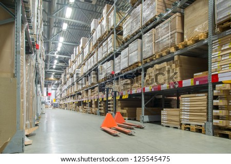 Rows of shelves with huge cardboard boxes and orange storage carts on floor in modern warehouse - stock photo