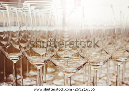Rows of Shiny Empty High Glasses with Reflections in Restaurant close up. Catering Concept. Image toned. - stock photo