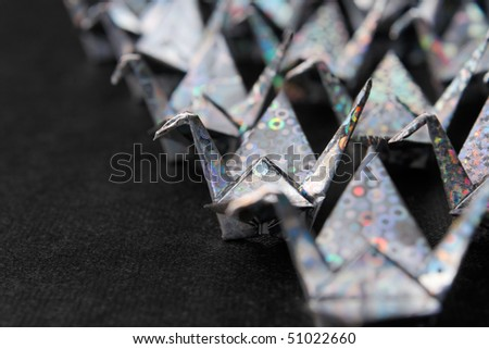 Rows of silver paper cranes facing the same direction. Shallow depth of field. - stock photo