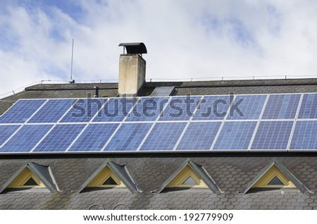 Rows of solar panels on the roof of big house - stock photo