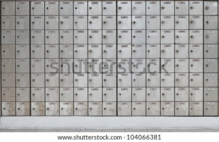 Rows of stainless steel post office box on a wall.