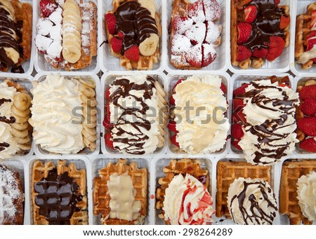 Rows of take away street waffles topped with strawberries, chocolates and whipped cream in Brussels of Belgium. - stock photo