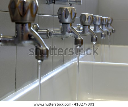 rows of taps in the bathroom of kindergarteners - stock photo