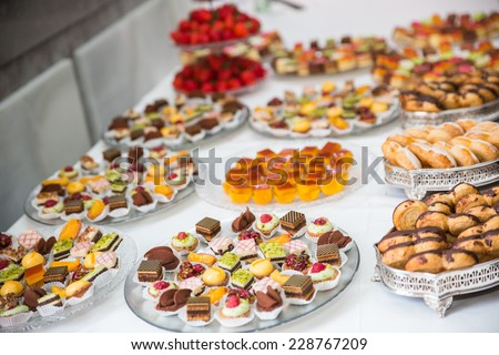 Rows of tasty looking desserts in beautiful arrangements. Mini desserts on catering buffet white tablecloth. Sweets on banquet table - picture taken during catering event - stock photo
