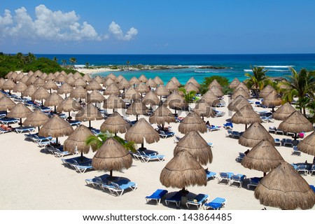 Rows of the palm leaf sun shades on the beach in Riviera Maya - stock photo