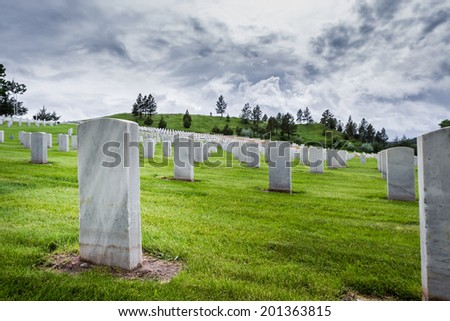 rows of tombstones in a military graveyard with bright green spring grass and dramatic storm clouds - stock photo