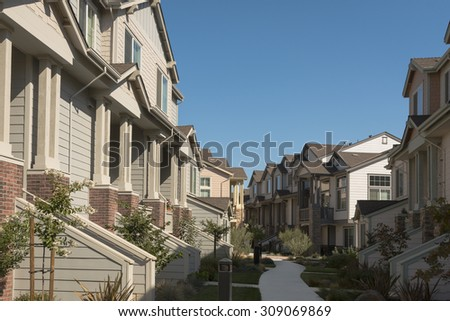 Rows of townhomes facing each other with a concrete path down the middle. - stock photo