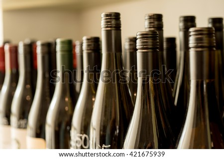 Rows of unlabeled and unopened bottles of wine - stock photo