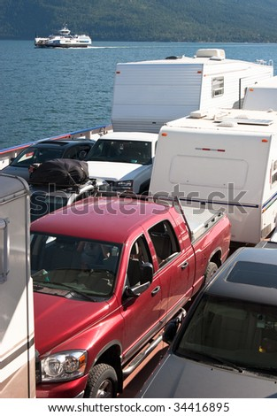 Rows of vehicles on a ferry with passing ferry in background - stock photo