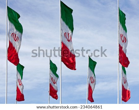 Rows of waving Iranian flags against cloudy blue sky. - stock photo