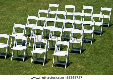 Rows of white empty chairs on a lawn before a wedding or ceremony - stock photo