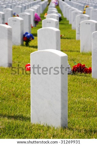 Rows of white granite headstones in a USA National Military Cemetery after Memorial Day (shallow focus on foreground headstone). - stock photo