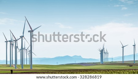 Rows of wind turbines on green boundless fields on background of blue cloudy sky and distant hills. Alternative energy source, production and power generation. Ecology and environment. - stock photo