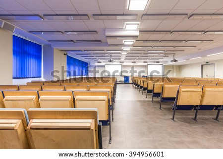 Rows of wood chairs in spacious, light auditorium with blue details