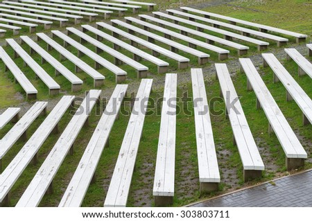 Rows of wooden benches on hillside of outdoor concert area, wet seats after rain - stock photo