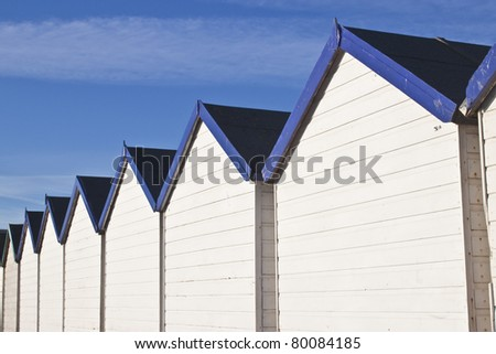 rows of wooden white and blue beach huts - stock photo