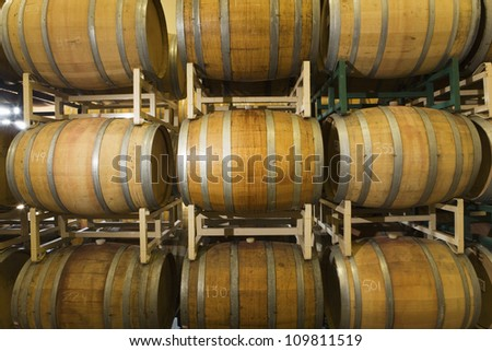 Rows of wooden wine barrels in winery cellar