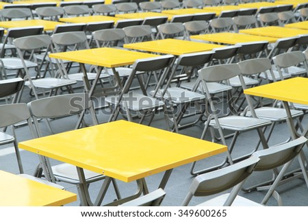 Rows of yellow metal tables and chairs