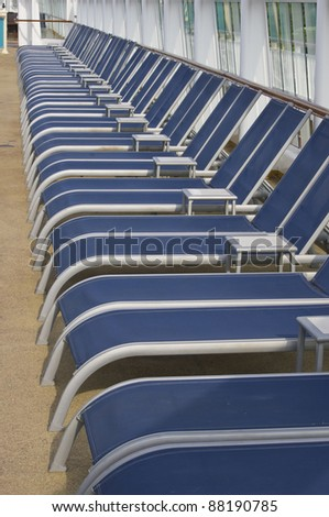 Royal blue lounge chairs for lying in the sun on a cruise ship deck - stock photo