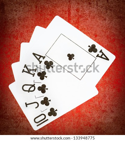 Royal flash of clubs on grunge poker table - stock photo